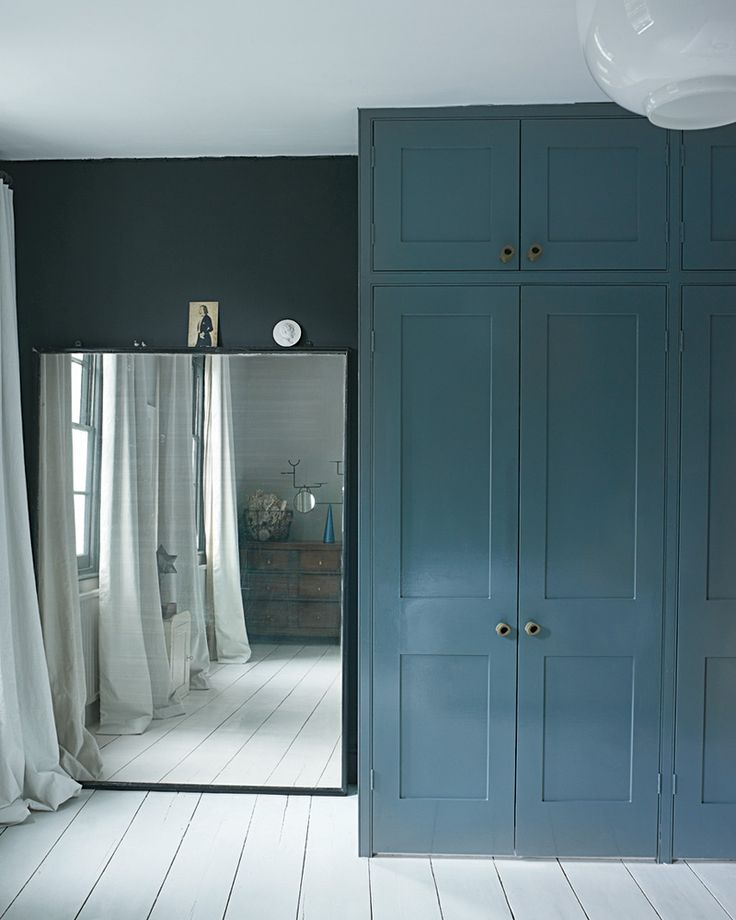 Blue-grey bedroom, wardrobes, white floorboards, vintage mirror. Faye Toogood - T Magazine