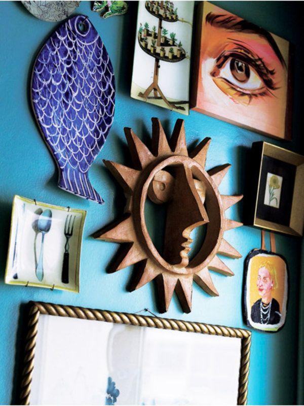 キッチンの壁に飾ったコレクションが、このコーナーをいっそう輝かせる。青いセラミックの魚、1970年代のカリフォルニアを思い出させる木製の太陽、インドの映画スターの目の絵などが交ざり合っている。 部屋に飾られるいくつかのアートも、実はもともと撮影のために作ったもの。たとえばフレームに入れられた詩は、アンティークの本を切り抜き、黒い花の絵で彩った。まるでイギリスのアーティスト、ヒューゴ・ギネスの作品のように。