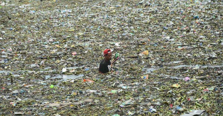 20160801 - Homem coleta material reciclável em canal repleto de lixo no centro de Manila, capital das Filipinas Imagem: Ted Aljibe/AFP