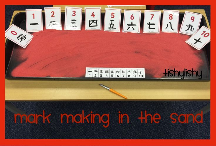 Mark making in the red sand. Number cards from Twinkl
