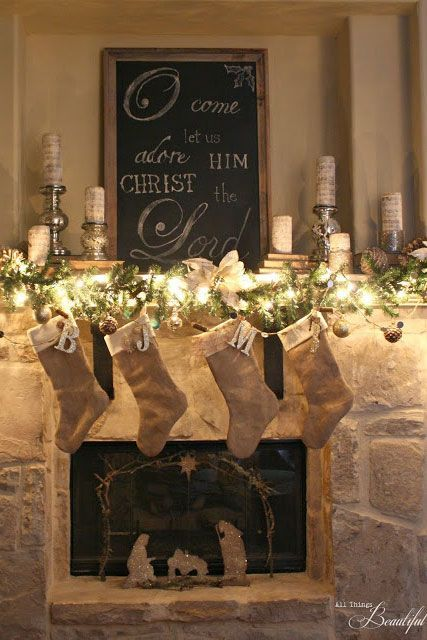 An oversized sign flanked by beautiful votives takes this mantel from rustic to elegant.