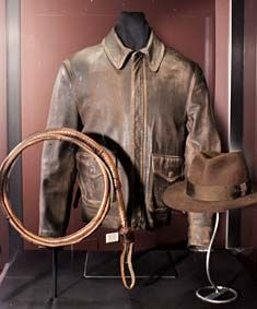 Fedora, jacket, and whip used by Harrison Ford in the 1984 Indiana Jones trilogy. Costume designed by Deborah Nadoolman.