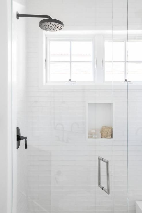 An oil rubbed bronze shower head is fixed to long white shower ...