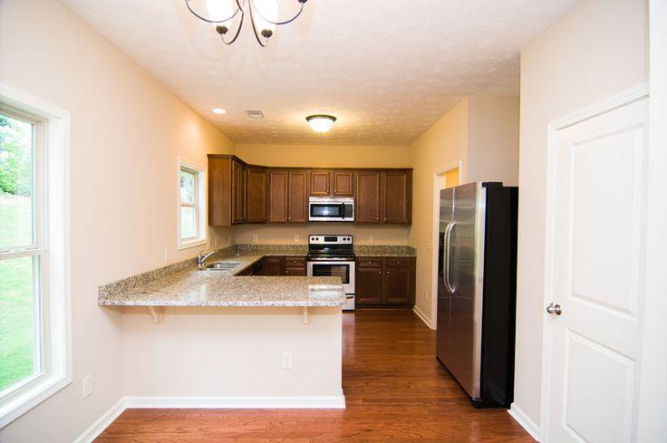 """Kitchen with wrap-around countertops inside """"The Azalea"""". Wall color is Sherwin Williams SW6106 Kilim Beige. Cabinets are Integrity Sedona Espresso. Countertops are Giallo St. Cecelia Light granite."""
