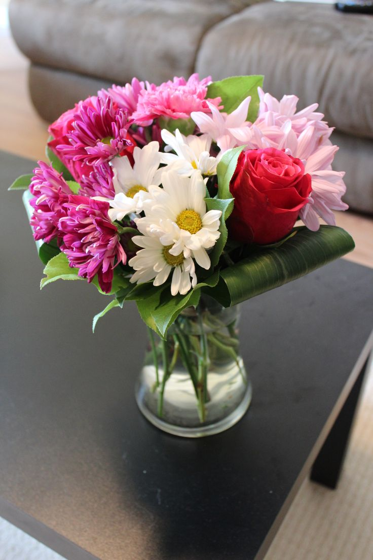 Vase arrangement in shades of pink with daisies and roses.