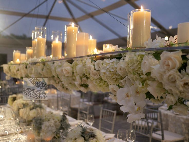 Suspended centerpiece with flowers on bottom and candles on top.