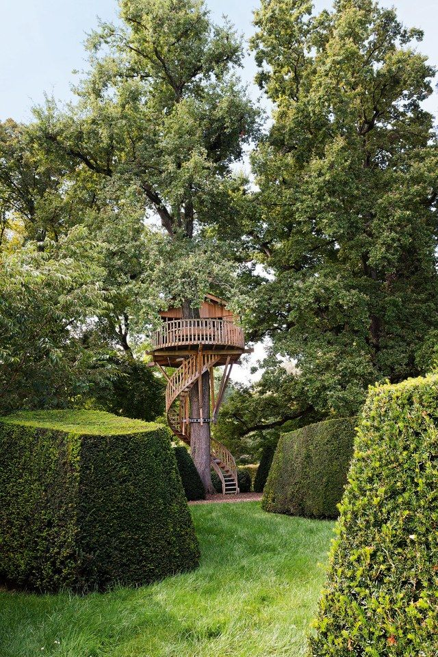 In the gardens of an old converted farmhouse in Geneva, Switzerland, a small cabin adheres to the natural setting with a curvilinear concept that encircles the trunk of an old oak tree. | archdigest.com