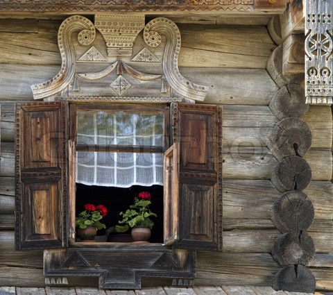 Wooden wall of old Russian house with flowers in the window sill, lovely!