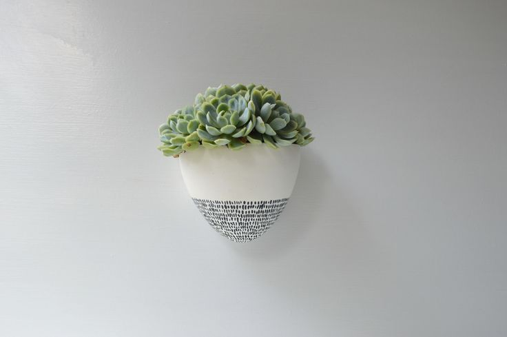 This pure white clay has been painted with a satiny white glaze This pot is ready for your own greenery, whether that be a succulent, cactus or whatever you love.To create the textured dashes I have used black pigment mixed with a glaze and hand painted them onto the planter.Screws are included for easy hanging. EnjoySize : 120 mm wide x 110 mm deep and 120mm height