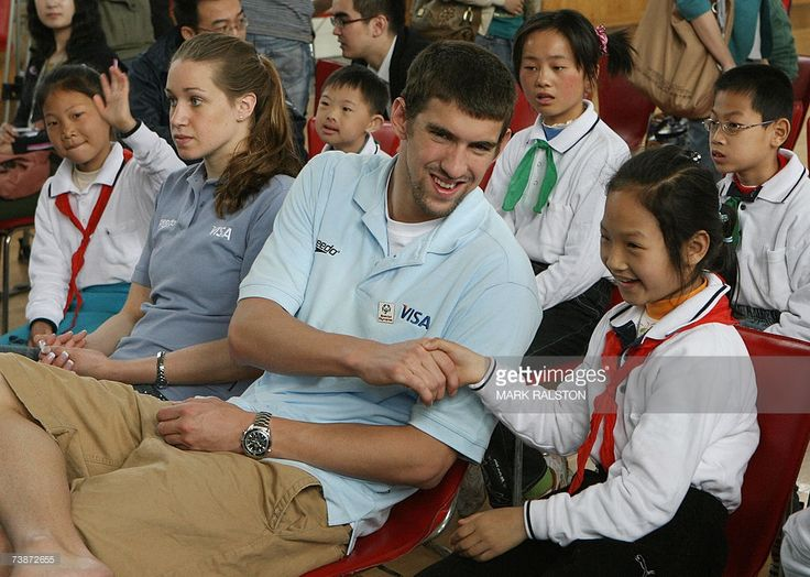 Olympic and World Swimming champions Katie Hoff (3rd R) and Michael Phelps (C), sit with disabled students from the Pudong Special Needs School in Shanghai, 13 April 2007. Phelps and Hoff are in Shanghai on a goodwill tour to promote the 2007 Special Olympics to be held in October. AFP PHOTO/Mark RALSTON