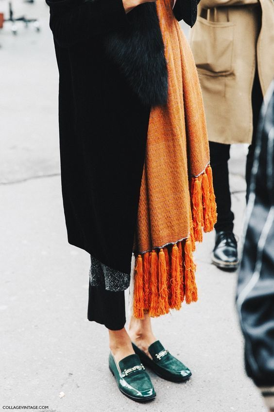 Straight legged trousers with a long black duster coat, complete with a splash of colour: a long orange scarf with emerald brogues