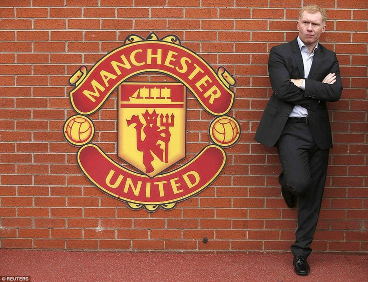 Former United midfielder Paul Scholes stands next to the United club crest in front of the dug out.