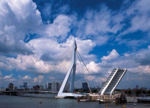 """The Erasmus Bridge is a cable stayed bridge across the Nieuwe Maas river. The Bridge was designed by Ben van Berkel and completed in 1996. The 808 metre long bridge has a 139 metre-high asymmetrical pylon, earning the bridge its nickname of """"The Swan"""". The southern span of the bridge has a 89 metre long bascule bridge for ships that cannot pass under the bridge. The bascule bridge is the largest and heaviest in West Europe and has the largest panel of its type in the world."""