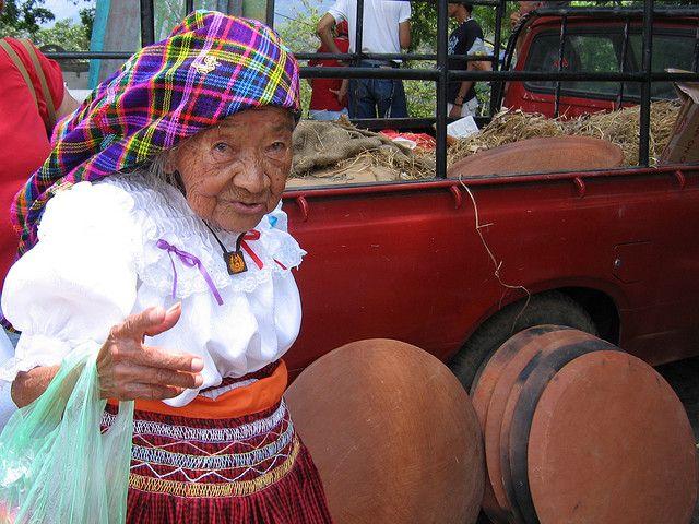 Anciana mostrando su traje tradicional en Panchimalco, San Salvador, en segundo plano se observa la venta de comales de barro. Foto Mario Salazar G