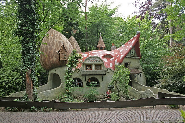 A house with seven gnomes in De Efteling. One is fishing outside, one is looking out of the window, one is sleeping, one is reading, one is ill, one is reading and the last one is enjoying a pipe.