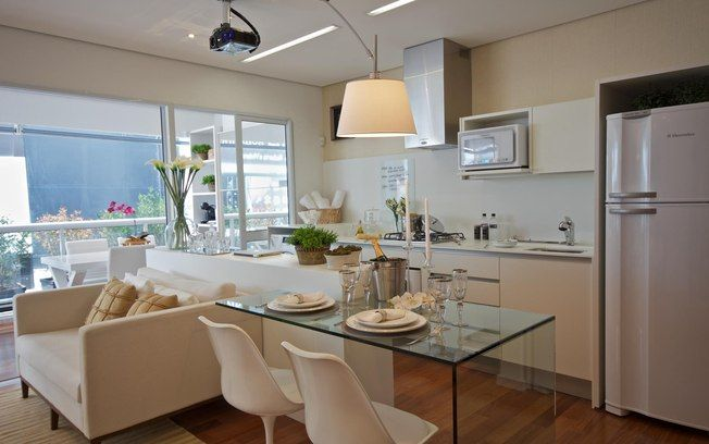 A bancada de Corian e a mesa de vidro separam a cozinha da sala de estar. Ao fundo, o micro-ondas ao lado do fogão. Foto: Divulgação