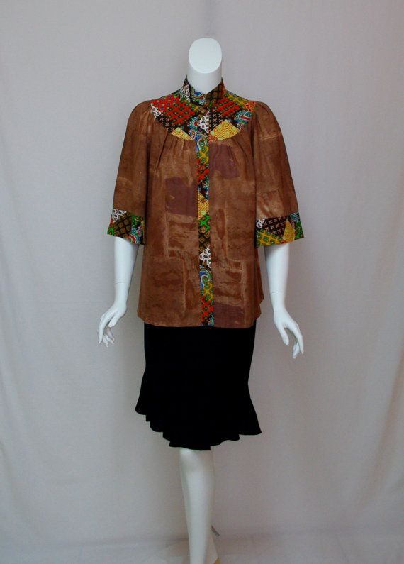 Vintage Brown Smock Top Brown with Patchwork Print Trim 1970s  MEASUREMENTS in inches: Shoulders: 14 Bust: 44 Waist/hips: Free Sleeve: 16-3/4 Sleeve opening: 12-3/4 Bottom/hem: 54 Collar: 1-5/8 Sleeve trim: 3  Condition: Unused, unwashed condition with no issues to note.