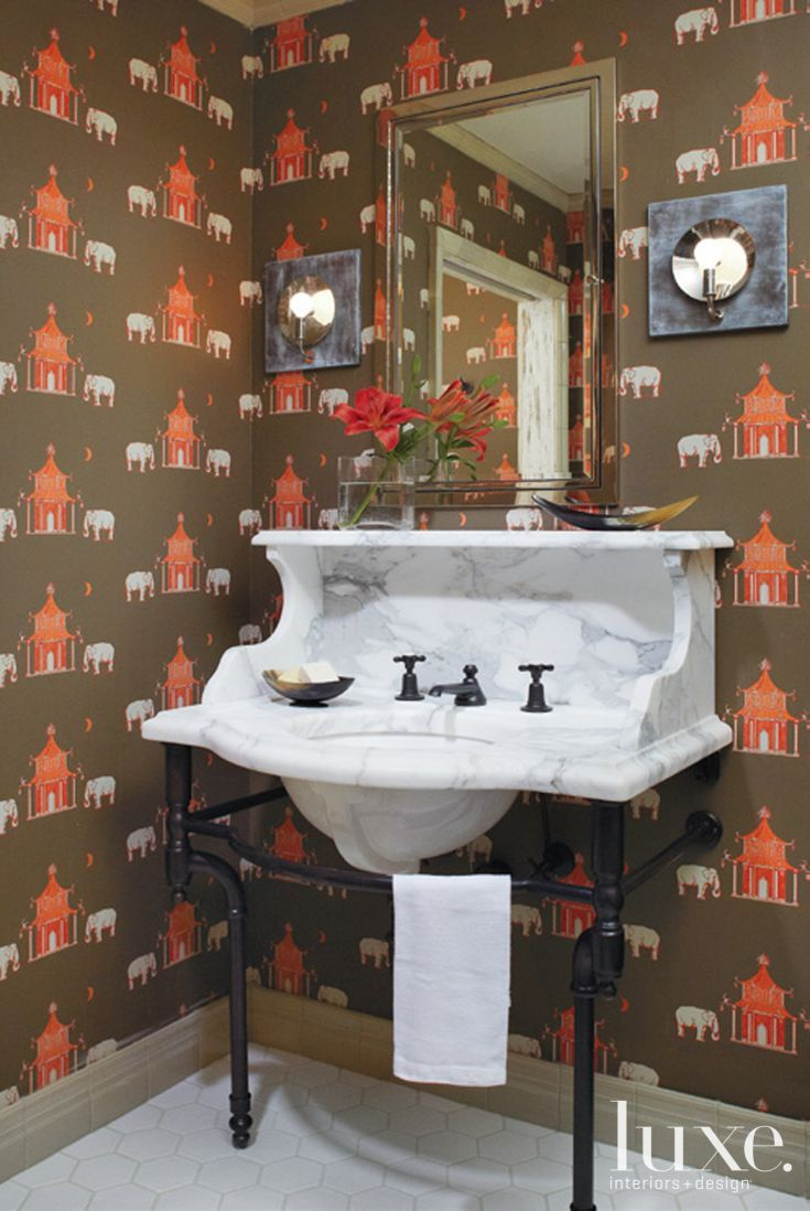 A Victorian-influenced washstand, Waterworks fixtures, playful Katie Ridder wallcovering and a Restoration Hardware mirror produce a hip master bath.