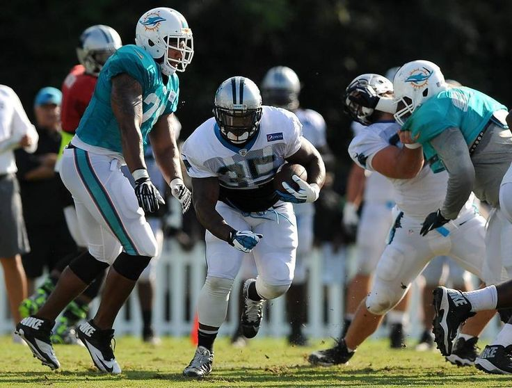 Carolina Panthers full back Mike Tolbert, center, breaks through a hole in the Miami Dolphins defense during practice on Thursday, August 20, 2015. The Panthers hosted the Miami Dolphins in a joint practice at Wofford College in Spartanburg, SC.