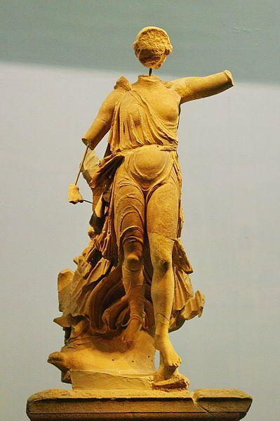 """La """"Nike in volo"""" è l'unica scultura accertata dello scultore Peonio. La statua è in marmo scolpito a tutto tondo ed è stata realizzata intorno al 421 a.C, infatti fu commissionata dai cittadini di Messenia e Naupacto per commemorare la vittoria sugli Spartani. Ora si trova al Museo Archeologico di Olimpia."""