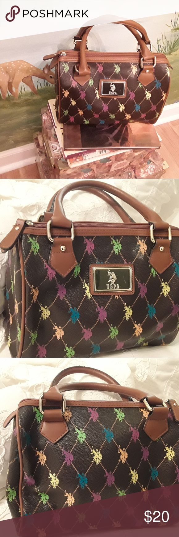 HANDBAG BY U.S. POLO ASSN. BROWN /MULTI COLOR I HAVE FOR SALE A BROWN /MULTI COLOR HANDBAG WITH GOLD HARDWARE.  THIS BAG IS IN LIKE NEW CONDITION, IT HAS NEVER BEEN USED. IT IS A GREAT SIZE IT CAN HOLD A LOT.   THE BAG HAS ZIPP TOP CLOSUR AND INSIDE IT HAS ON ONE SIDE A ZIP POCKET AND ON THE OTHER SIDE IT HAS TWO OPEN POCKETS FOR CELL PHONE ECT.  U.S.POLO ASSN. IS NOT AFFILIATED WITH POLO RALPH LAUREN.  IF YOU HAVE ANY QUESTIONS ABOUT THIS ITEM PLEASE ASK. THANKS FOR SHOPPING MY CLOSET. U…