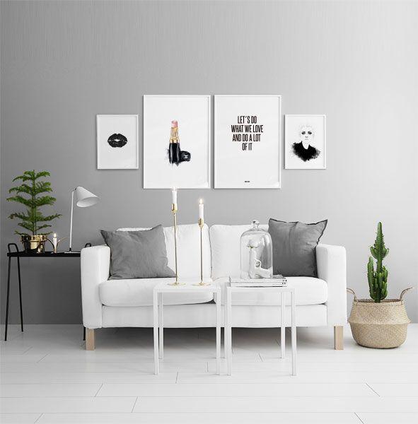 Tavelvägg ovanför vit soffa. Posters och prints i vita ramar. 30x4cm0 och 50x70cm