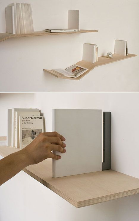 """V-Shelves - A laminated plywood shelf that has a gentle """"v"""" at one end to enable the user to display an open book. The two wall-fixation components that resemble books in shape and size also act as bookends."""