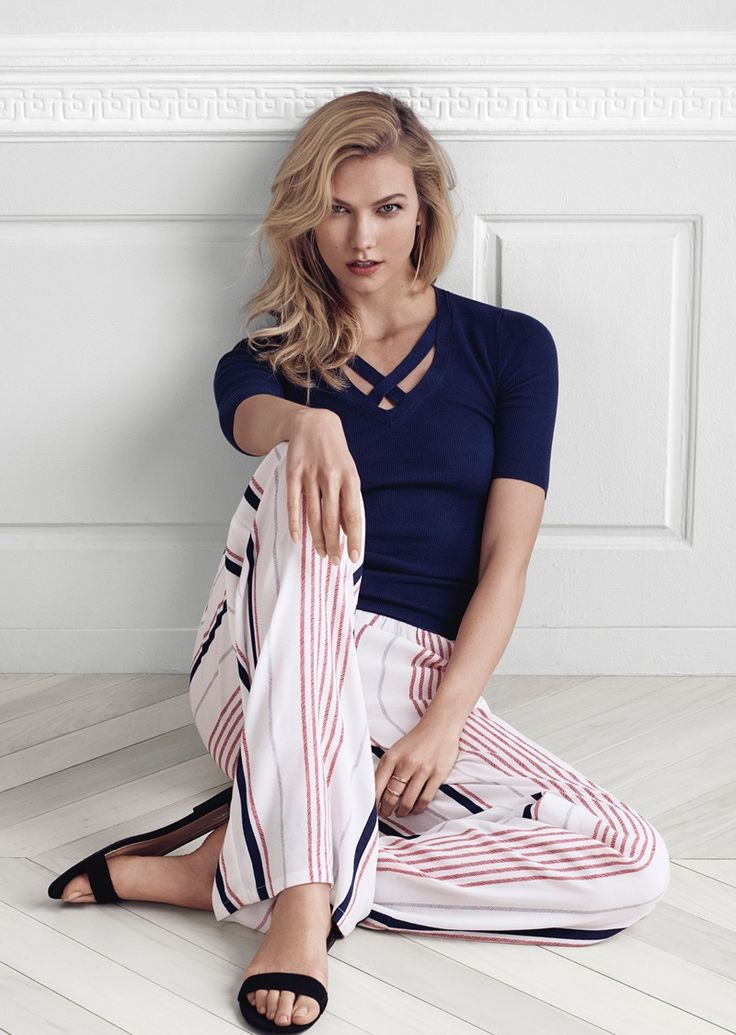 Karlie Kloss poses in Express Elbow Sleeve Crossover V-Neck Sweater and Wide Leg Stripe Dress Pant