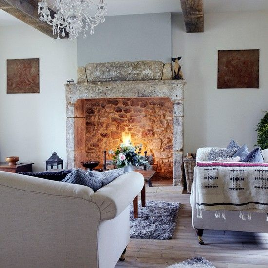 A colour palette of blues, greys and limed wood contrasts with the exposed beams and stone fireplace inthis country living room. A large open fire creates a stunning focal point, adding warmth to this sophisticated scheme.