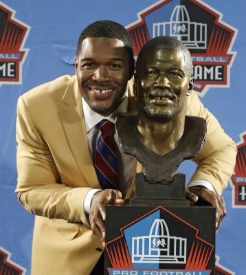 Hall of Fame inductee Michael Strahan poses with his bust during the Pro Football Hall of Fame enshrinement ceremony Saturday, Aug. 2, 2014, in Canton, Ohio.