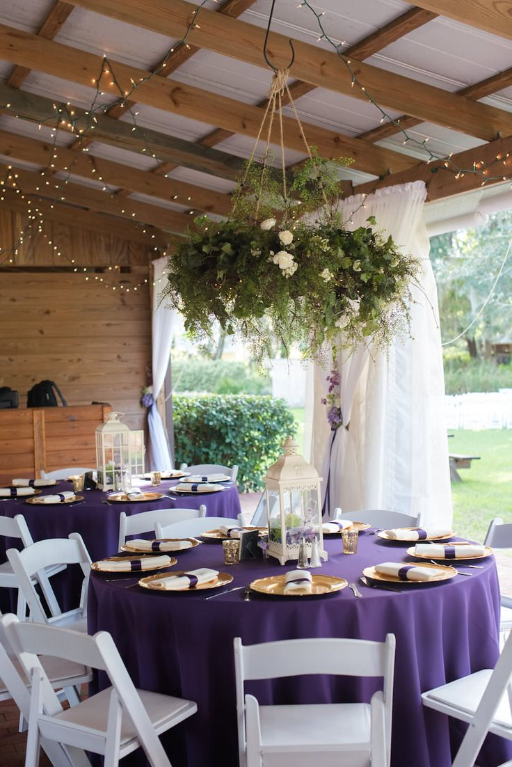 White Lantern Wedding Centerpieces with Gold Chargers on Purple Linens with White Resin Folding Chairs and Hanging Greenery Centerpiece Suspended from Ceiling | Tampa Bay Wedding Venue Cross Creek Ranch
