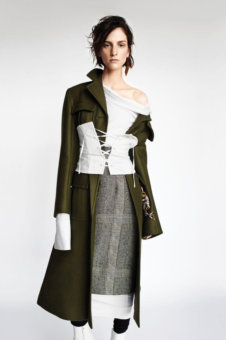 Prada's double-faced wool coat, denim corset, and charms; Jil Sander's cotton poplin shirt; Creatures of the Wind's polyester, cotton and silk herringbone plaid skirt. Ana Khouri earring.