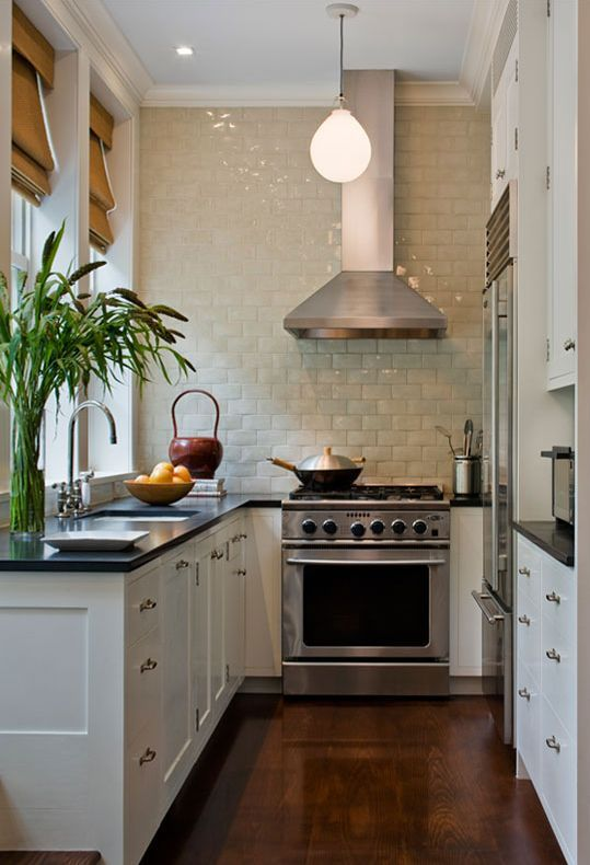A really great small kitchen with white subway tile all along the back wall, dark countertops and white cabinets.