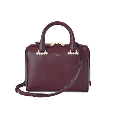 Our Mini Pearl Bowling Bag is a modern take on vintage sophistication with a minimal aesthetic. Handmade from the finest smooth burgundy Italian calf leather and exquisitely adorned with delicate pearl detailing, this versatile bowling style bag...