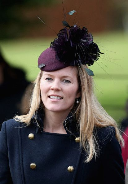 Autumn Phillips in an exquisite purple hat with a large oversized flower decoration.