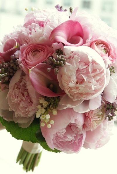Rose carried a soft and sweetly scented bouquet of blush peonies, ranunculus, and mini calla lilies with accents of lavender lilac and precious lily of the valley finished by a green ruffled collar of galax foliage