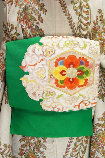 優美に蔓をまくアラベスクと、華やかな唐花で彩られた大きな雪輪文様が織り出された綴織調の正絹開き名古屋帯です。