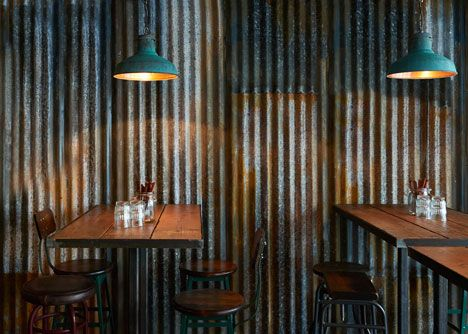 Interior designers Brinkworth have created a restaurant in central London Barnyard Soho that resembles a farm building, with rusty corrugated iron on the walls and salvaged lighting