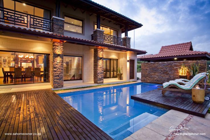 stone wall behind the pool and deck over hanging the pool is a great idea