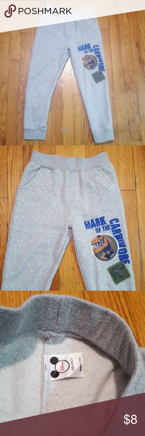 Disney's The Good Dinosaur Joggers Boys, light gray dinosaur slim fit joggers. They are 55% cotton and 45% polyester. Disney Bottoms Sweatpants & Joggers