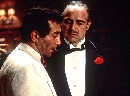 """Don Corleone:  """"You look terrible. I want you to eat, I want you to rest well. And a month from now this Hollywood big shot's gonna give you what you want."""" Johnny Fontane:  """"Too late. They start shooting in a week."""" Don Corleone:  """"I'm gonna make him an offer he can't refuse. Okay? I want you to leave it all to me. Go on, go back to the party."""" (Marlon Brando and Al Martino as Vito Corleone and Johnny Fontane in """"The Godfather"""")"""