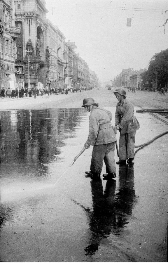 Aug 18 1943 - Leningrad . The siege continues , as Soviets fight back . Firefighter`s wash blood from the asphalt , on the Nevsky Prospekt in Leningrad - after people were killed - as a result of German shelling