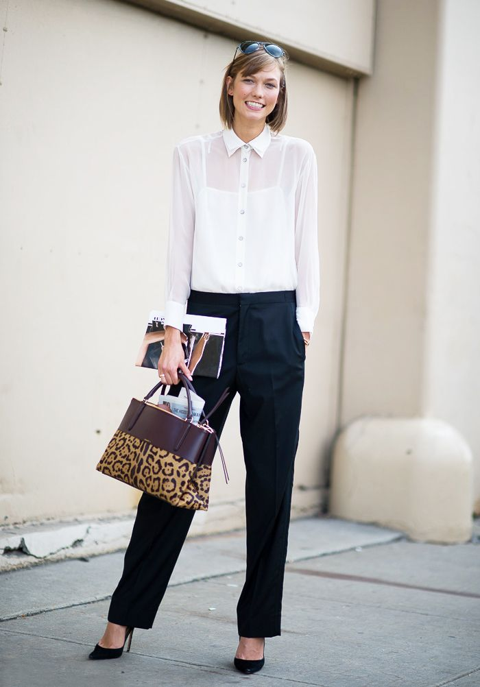 Karlie Kloss wearing a sheet white button-up top, black trousers, and a leopard print bag #streetstyle #work