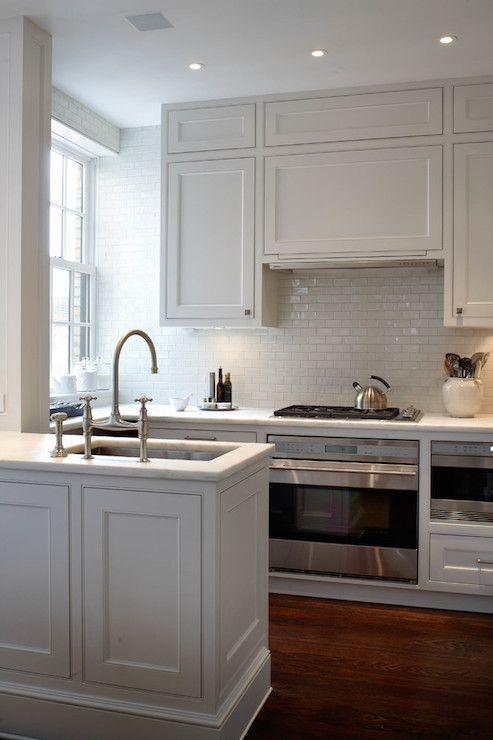 Amazing kitchen boasts creamy white shaker cabinets paired with honed white marble countertops and a white glazed mini subway tiled backsplash.