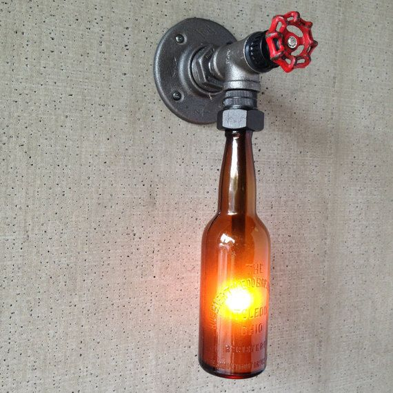 Pick out custom bottles through our Bottle Browser at: http://www.pearedcreation.com/product-category/bottles/ This is a hanging lantern made from a pre-prohibition brewery bottle. It uses a small incandescent bulb to give off an amber glow. The bottle is secured into an iron pipe base. A rotating faucet handle serves as a switch to turn the light on and off, a new feature we are excited about! Buyer has the option of powering via cord and plug or wiring direct.  Bulbs are easily…