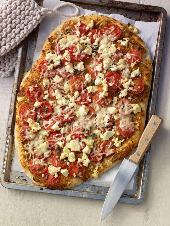 Pizza aus Hefeteig mit selbstgemachtem rotem Pesto, frischen Tomaten und Schafskäse