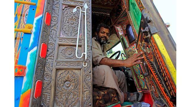Un conductor mantiene abierta la puerta de la cabina de madera tallada de su camión decorado en Faisalabad