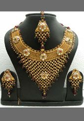 Jewellery set will be remembered for its great beauty and charming looks. Golden color polki necklace set designed with white polki, multi hue pota and artificial pearl work. Pair of designer chandelier earrings and maangtika is available with it. This set is electroplated with yellow radium polish.