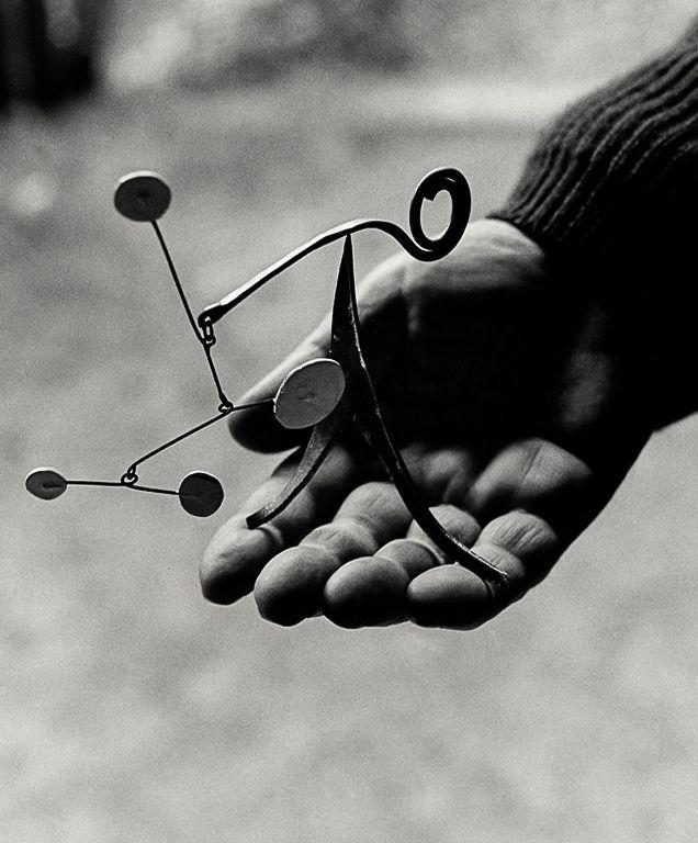 ALEXANDER CALDER, Calder holding one of his miniature mobile sculptures, Saché, France 1963. Photograph by Ugo Mulas.