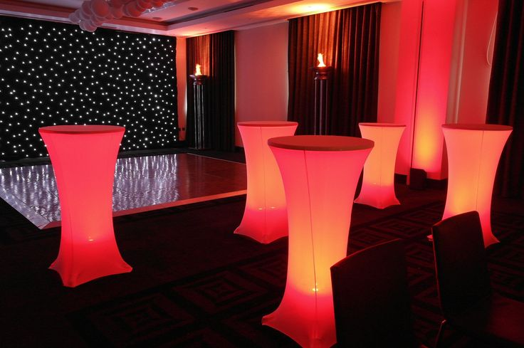 Starcloth backdrop, wall uplighters in red, illuminated poseur tables and silk flambeaux [via stressfreehire.com]